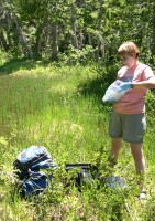 A USGS scientist is bagging up a sample while standing in a field of grass.