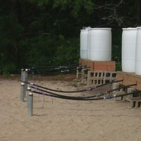 White tanks used to hold the tracer injection solutions with tubing going to injection wells