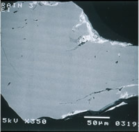 Electron photomicrograph of a cross section of a quartz grain from sediments on Cape Cod, MA, shows coatings (white material at the surface).  The coatings contain arsenic that can be released under changing chemical conditions.