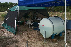 USGS scientists in a tent processing groundwater samples during a subsurface pH modification experiment.