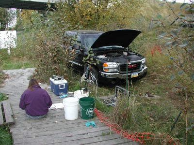 USGS scientist on a platform next to a wellhead with sampling equipment. SUV is in the backgroud