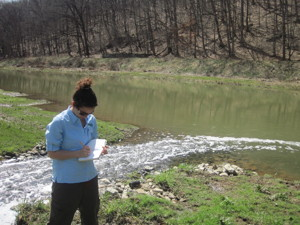 USGS scientist taking notes near a wastewater discharge