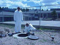 Scientists collecting a sample from a sewer.