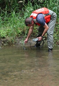 USGS scientist measuring pH and other water properties on the banks of Fourmile Creek, Iowa, before collecting a sediment sample for laboratory biodegradation experiments.