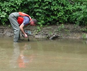 USGS scientist measuring pH and other water properties on the banks of Fourmile Creek, Iowa