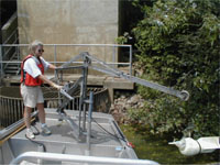USGS technician on a water-quality sampling boat is operating a water-quality sampler
