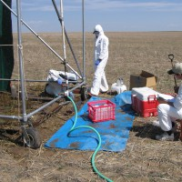 Scientists collecting samples of runoff from a test plot during a simulated rainfall event