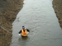 A USGS scientist is getting ready to measure discharge in a stream.