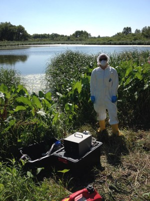 Scientist with full personal protective equipment Foreground sampling equipment - Background pond