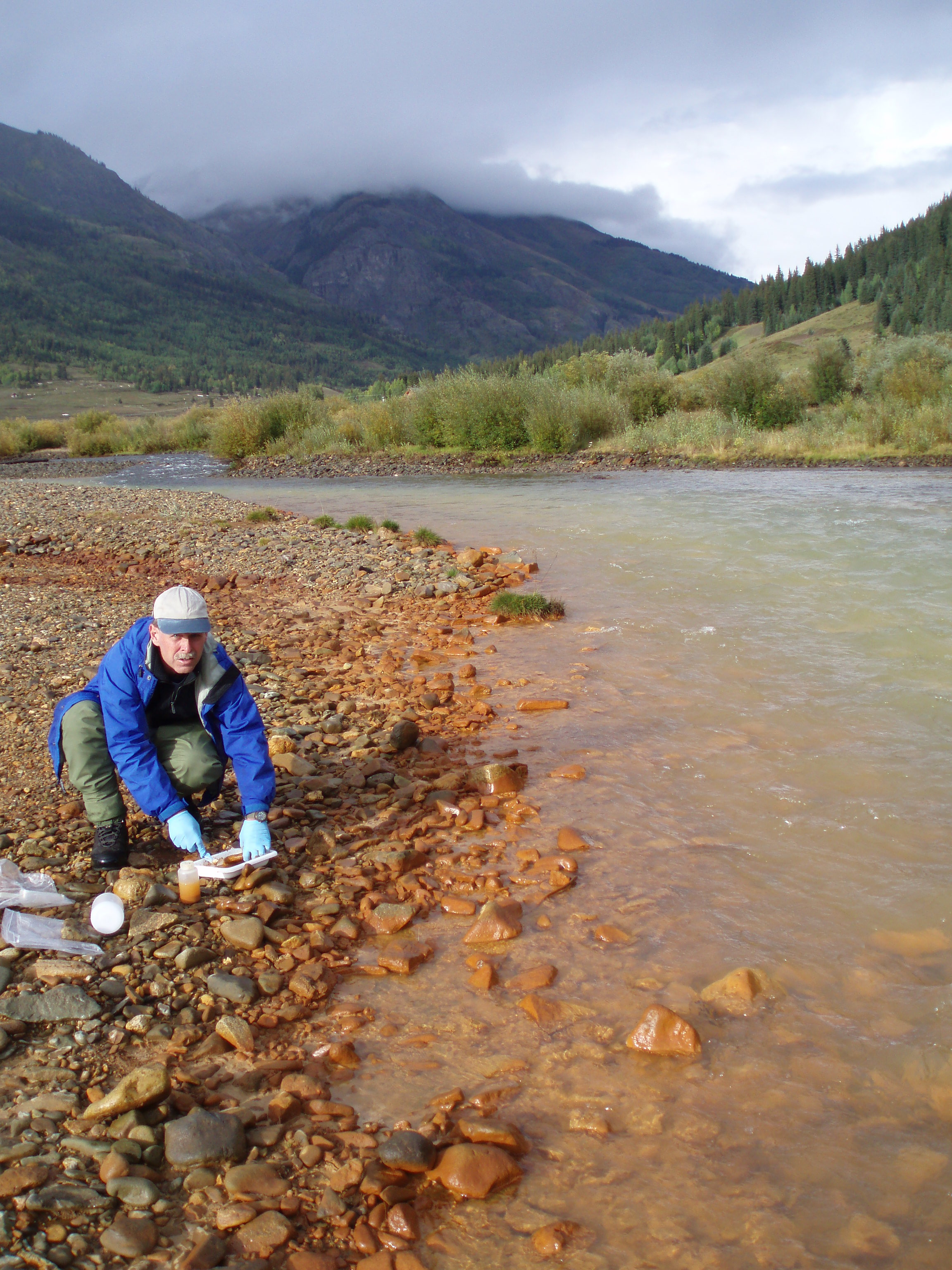 USGS scientist collecting a water sample from a gravel bar on side of a river.