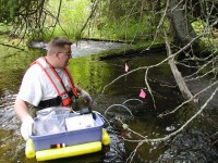 USGS scientist collecting samples of aquatic species from the Pike River, Wis.