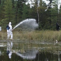A scientist in white protective suite applying a solution of water with sprayer