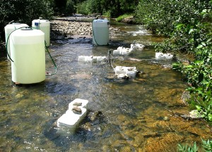 A stream with white water tanks on the side and small exposure containers