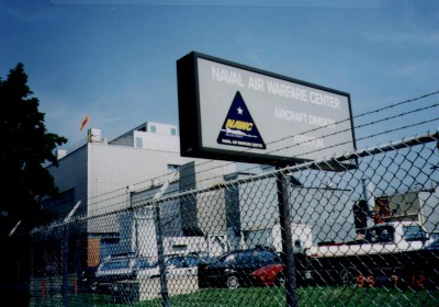 A sign behind a fence identifying the Naval Air Warfare Center (NAWC), West Trenton, NJ.