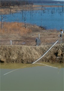 A brine pit - pit and berm in foreground - Skiatook Lake, Okla. in background