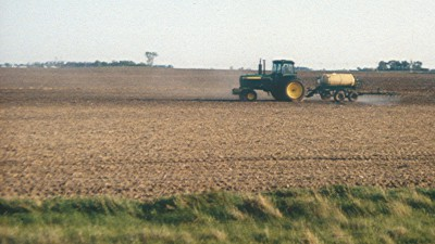 Farm field with tractor applying herbicides