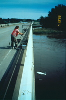 USGS scientist lowering a water-quality sampler into the Iowa River