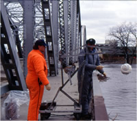 USGS technicians collecting water samples from a bridge