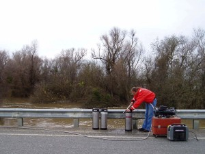 USGS scientist collecting a suspended sediment sample from the Yolo Bypass, Calif. The scientist is pumping water from the Bypass into stainless steel soda kegs. The large-volume water samples collected during the project were then centrifuged to separate suspended sediment from the water.