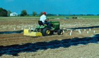 A small tractor with a tiller attachment on an test plot.