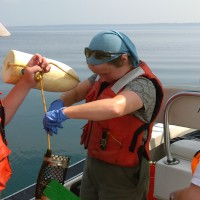 USGS scientists retrieve sampler from a boat