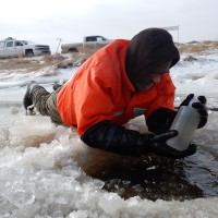 USGS scientist lifting a sample bottle from ice hole