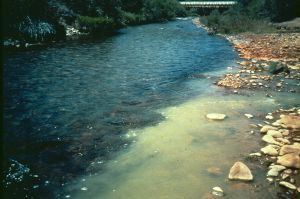 Acid mine                         drainage from California Gulch (right) mixes with the waters of the Arkansas River, Colorado (left).                         The chemical reactions that occurred as water from the Gulch mixed with the River's water controlled                         the quality of water downstream of the confluence