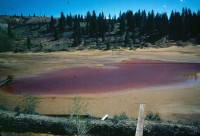 Tailings pile with a pond of red acidic water.