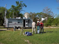 USGS scientists setting up mercury-aerosol sampling equipment in front of the USGS Mobile Atmospheric Mercury Laboratory at the Weeks Bay Estuarine Research Reserve, Mobile, Alabama